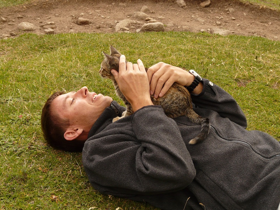 A man rubbing his cat